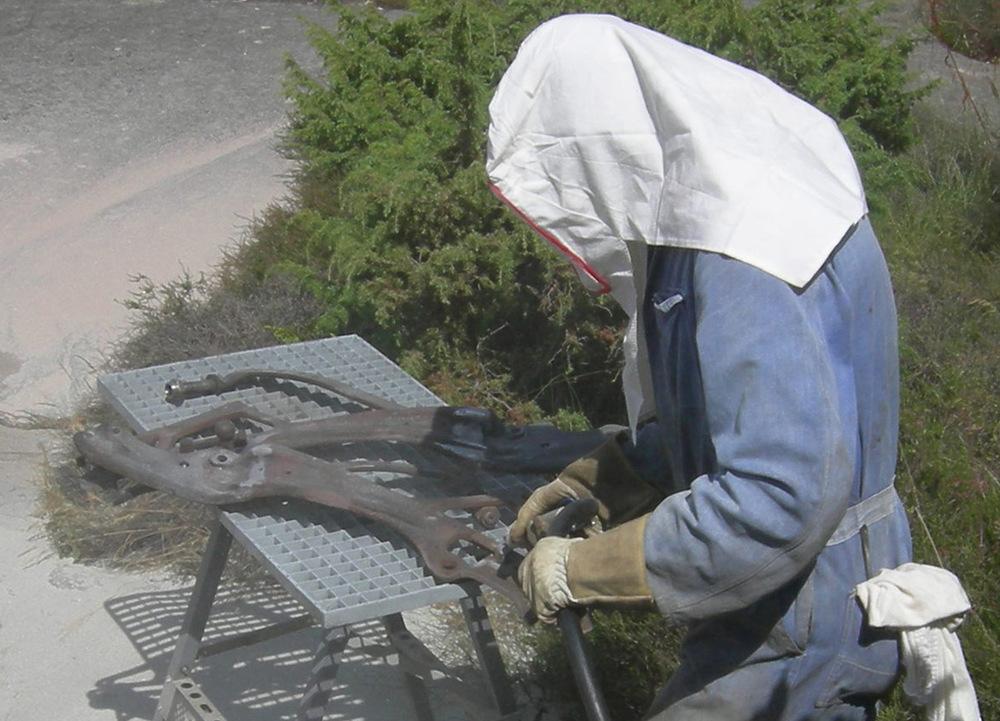 Kjell sandblåser delene på bildet over, etter at de er ferdig sveiset.