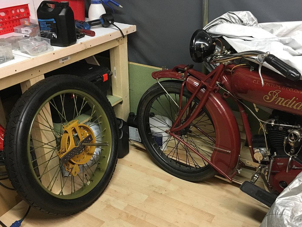 """Indian Powerplus 1000ccm 1919 modell vs Spanjola sidevognshjul. Indianeren var """"state of the art"""" innen motorsykler på den tiden. Det var fra Powerplus at Larsen valgte å bruke sylindere (2 par) til sitt prosjekt. Rjukan brannvesen anskaffet forøvrig 3 motorsykler med sidevogn av typen til aktiv branntjeneste spekket med brannutstyr. I tillegg til dobbelt motorvolum var """"alt"""" større på Spanjola. Hjulene er enorme. Brems på sidevognshjulet var høyst uvanlig så tidlig. Selv ikke Indian hadde det."""
