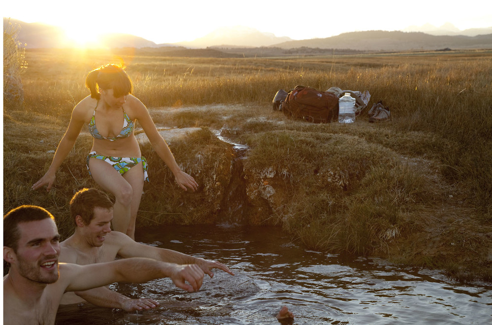 Lifestyle: Three friends enjoy a natural hot springs at sunset, Owens Valley, Eastern Sierras, California