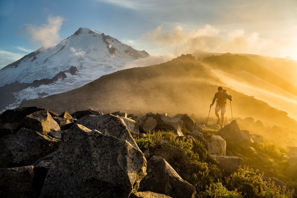 Adventure: Michael Hildebrand hiking through fog at sunset below Mt. Baker, Mt. Baker Wilderness, Washington