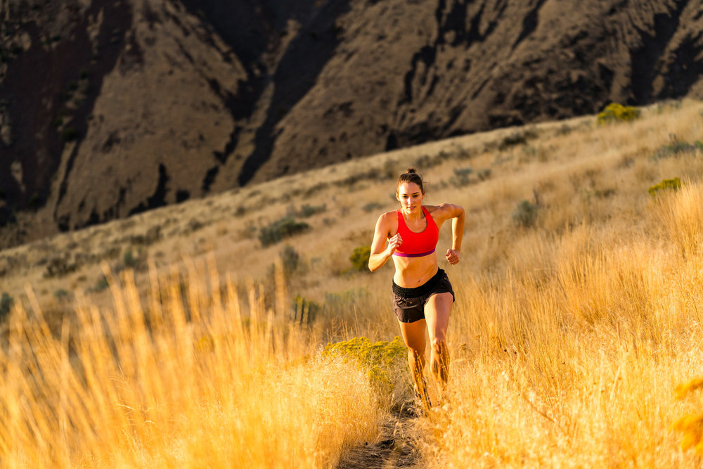 Adventure: A young woman trail running in late summer in Yakima Canyon, Washington