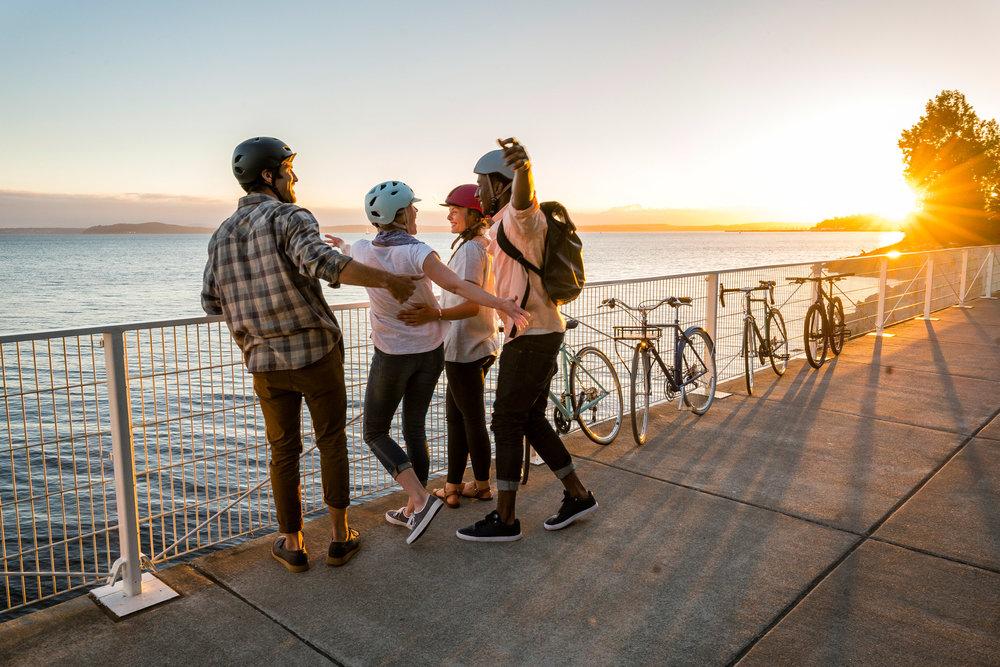 Lifestyle: A group of friends take a break from biking along the Seattle waterfront, Olympic Sculpture Park, Seattle