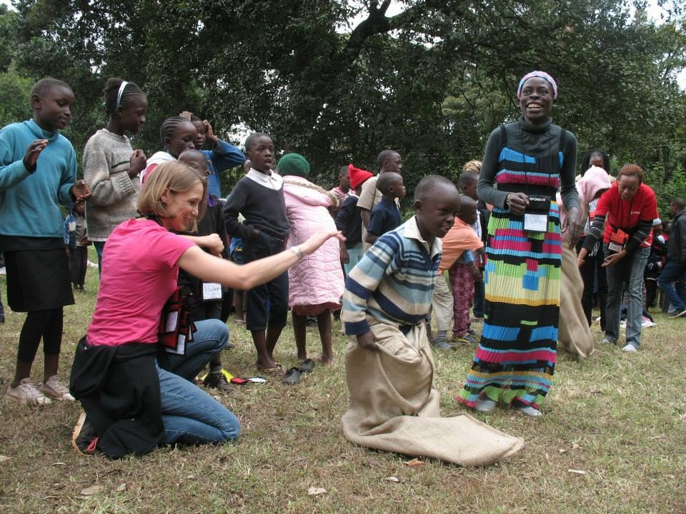 Lindsay helping children in sack races at camp in Kenya.
