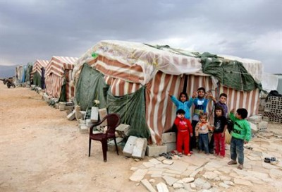 Syrian refugees children stand in front of their tents at a refugee camp last month in Arsal, a Sunni Muslim town eastern Lebanon near the Syrian border, that has become a safe haven for war-weary Syrian rebels and hundreds of refugee families — AP.