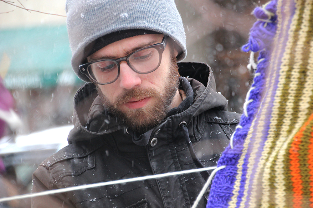 Jason Brown, co-chair of the Evanston, Ill. Public Art Committee, stitches pieces of fabric around a tree on Feb. 8, 2014 as part of a public art project. (ANNE EVANS/MEDILL)