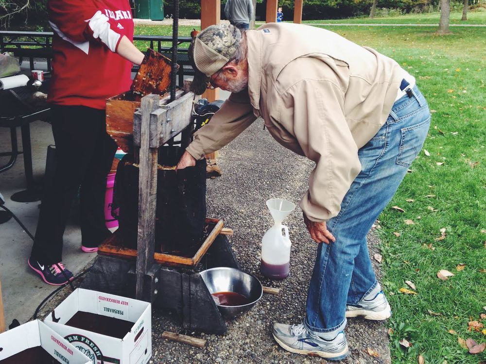 Volunteers keep the cider press running nonstop. The cider is then warmed, & volunteers fill their mugs before walking around the orchard.