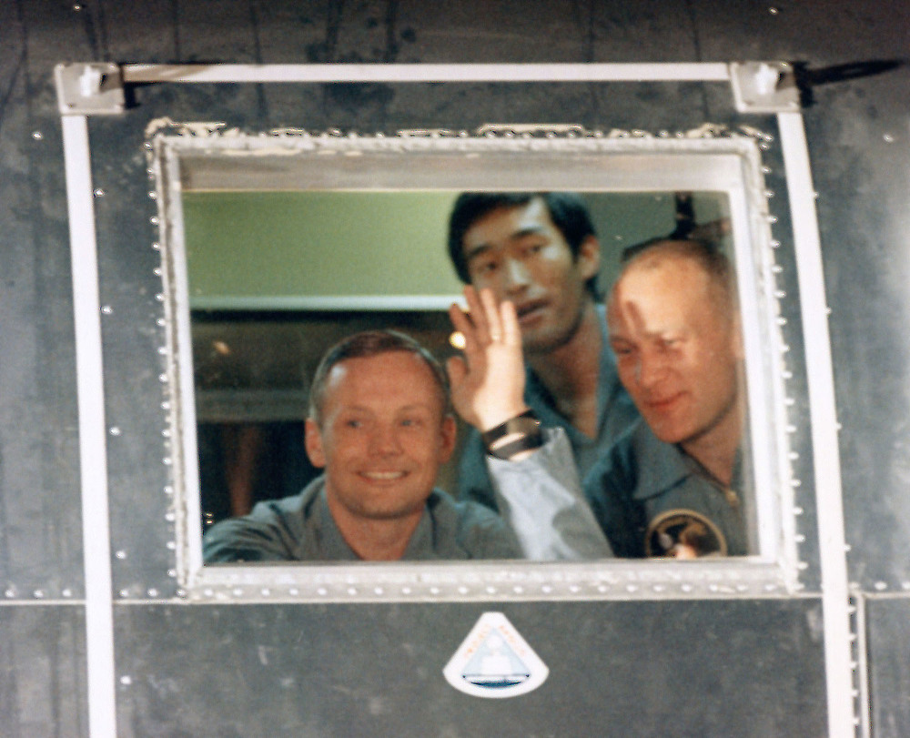 John Hirasaki looks over the shoulders of Neil Armstrong (waving) and Buzz Aldrin from within the MQF