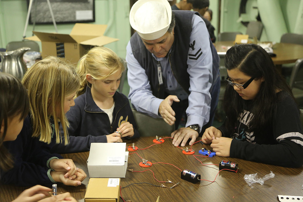 In a STEM electricity workshop,students work on designing and building simple series and parallel circuits by using components such as wires, batteries, and bulbs. |Photo by Keith Hedley