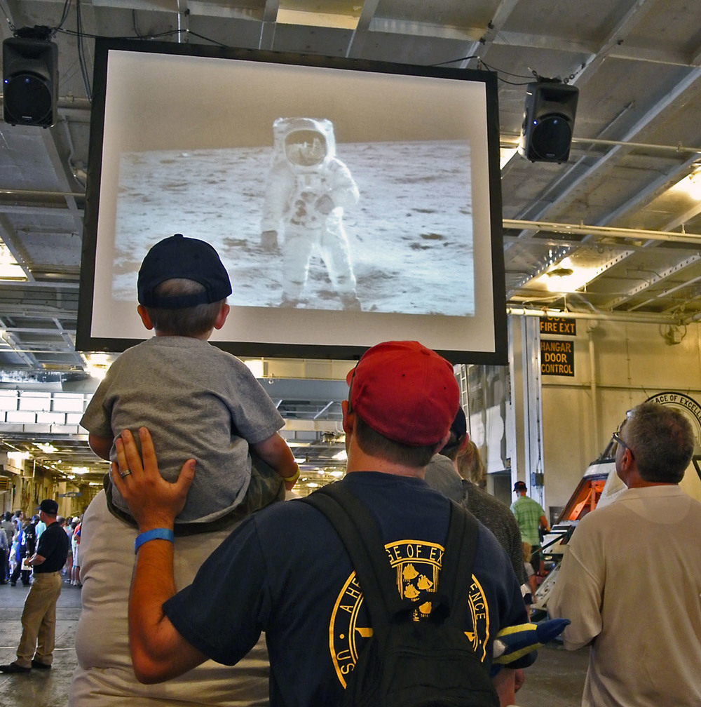 Father and son enjoy Buzz's presentation on a large screen