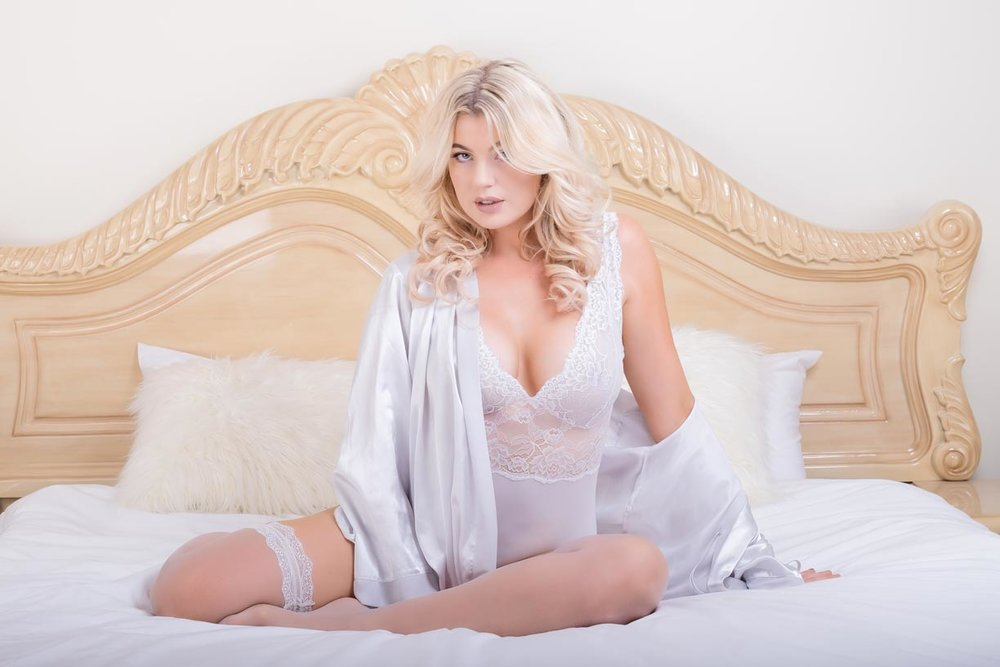 Brisbane bridal boudoir model sitting on a bed looking a the camera