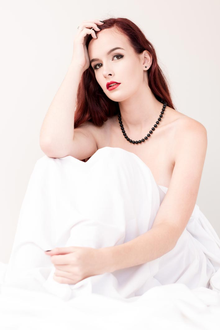 Brisbane boudoir model sitting under white bed sheets