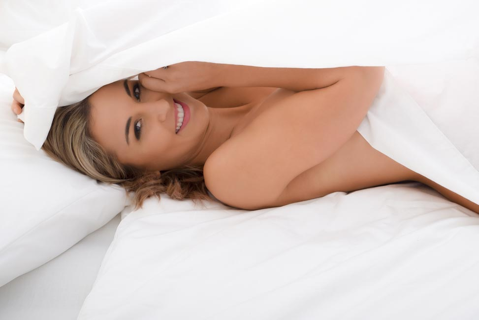Brisbane woman playing under white bed sheets for a playful bridal boudoir photo session