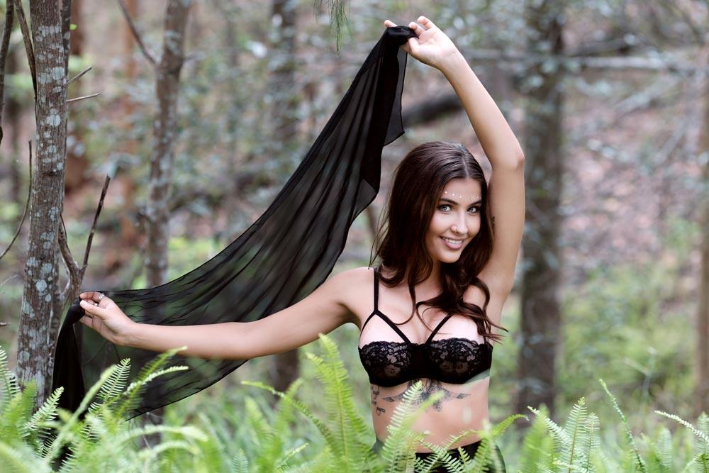 Brisbane boudoir model standing around green ferns with hands in the air