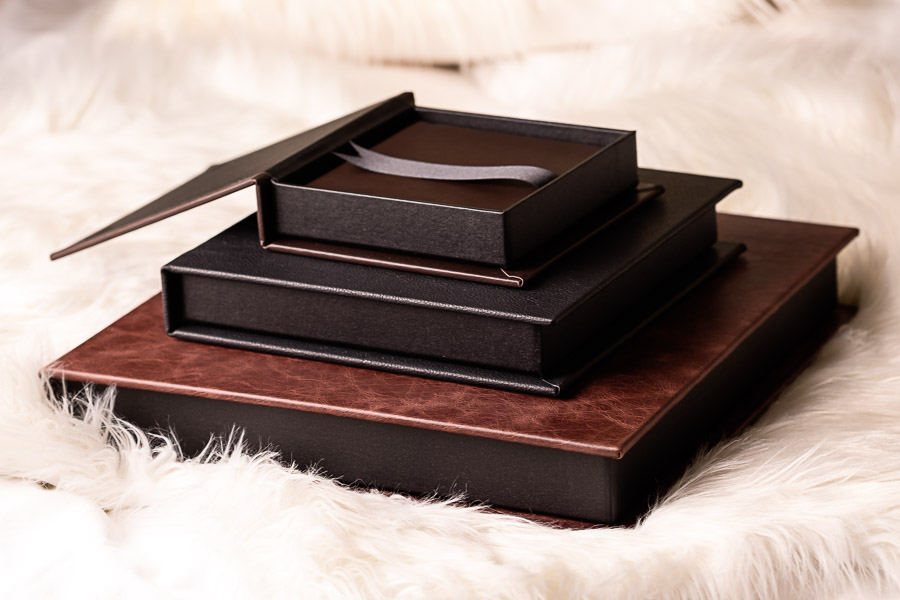 Three luxury leather boudoir albums on a bed