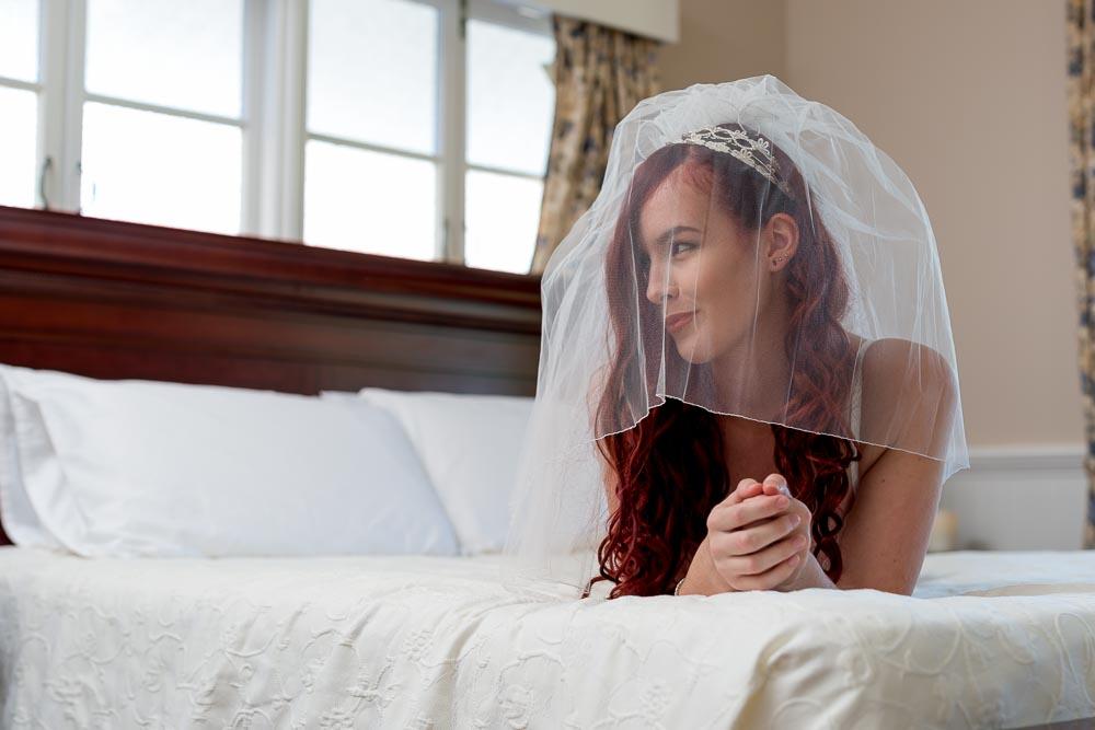 Brisbane woman posing for boudoir photos wearing a veil over her head