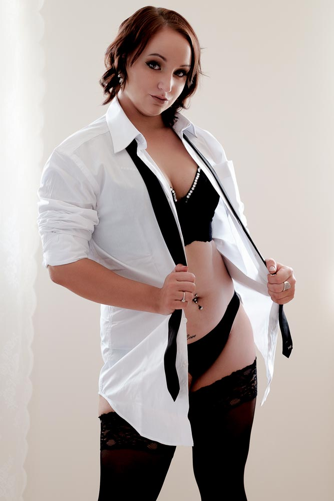 Boudoir model posing with her grooms white business shirt
