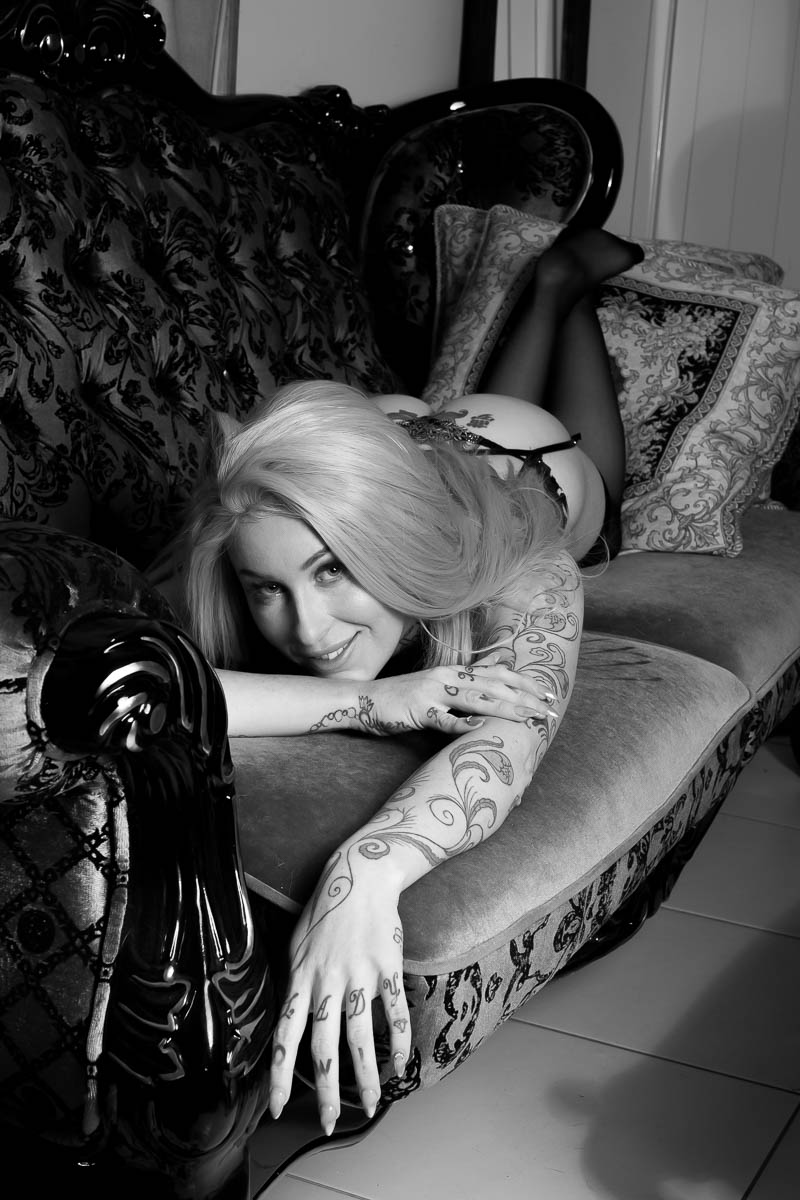 Black and white old Hollywood style boudoir photo of a Brisbane woman laying on a chaise lounge