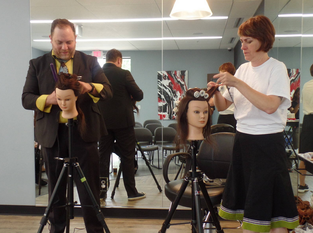 Ryan Teal (left) and DeAnna Teal (right) prep their mannequin heads before class beings.