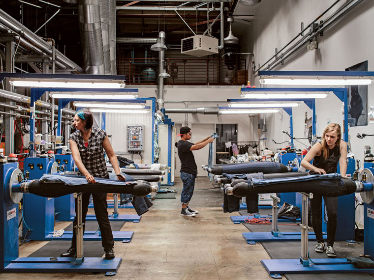 """Workers load jeans onto inflatable legs to experiment with creating different distressed looks. The best techniques, known as """"recipes,"""" are then replicated on a larger scale."""