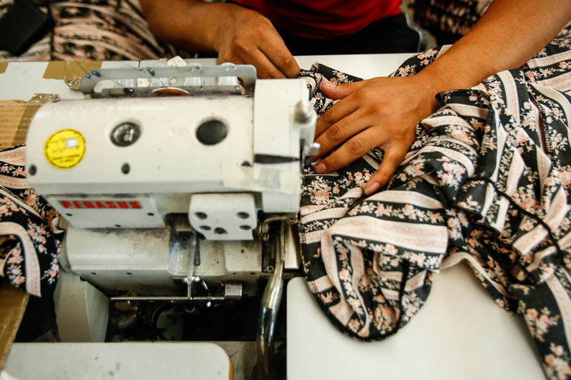 A worker sews garments inside a downtown Los Angeles factory. (Claire Hannah Collins / Los Angeles Times)
