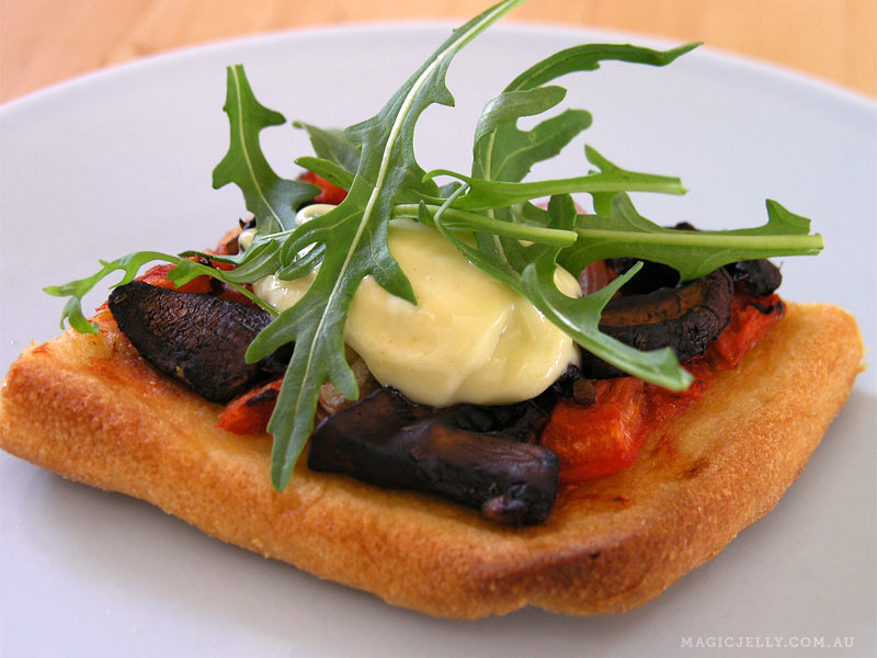 Cornmeal crust pizza. Mushrooms sauteed with garlic & balsamic vinegar, homemade lemony aioli & fresh rocket.