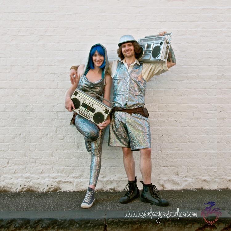Sea Dragon Skin's 'Disco Brawl' Holographic Festival Jumpsuit & Men's'Disco Brawl' Holographic Dancing Shorts & Dancing Vest.