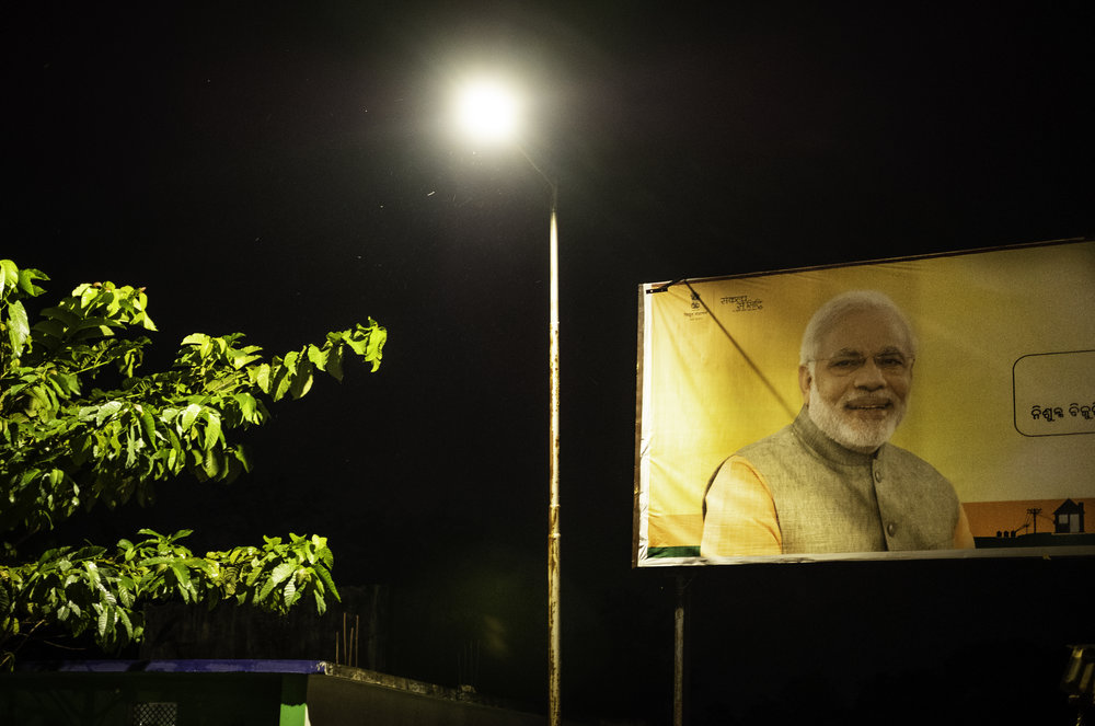 Indian Prime Minister Narendra Modi's photograph appears on many billboards throughout the Kandhamal area of India's Odisha state. During the Summer of 2008, men and women of Rashtriya Swayamsevak Sangh (RSS), a Hindu nationalist group, participated in three months of murder, rape, destruction, and torture against Christians in the Kandhamal and surrounding areas. Modi's election to office was largely due to the influence the RSS has in the majority Hindu India, and is now financially back by the Prime Minister's Bharatiya Janata Party, the largest political party in India.       Kandhamal, India. 2018