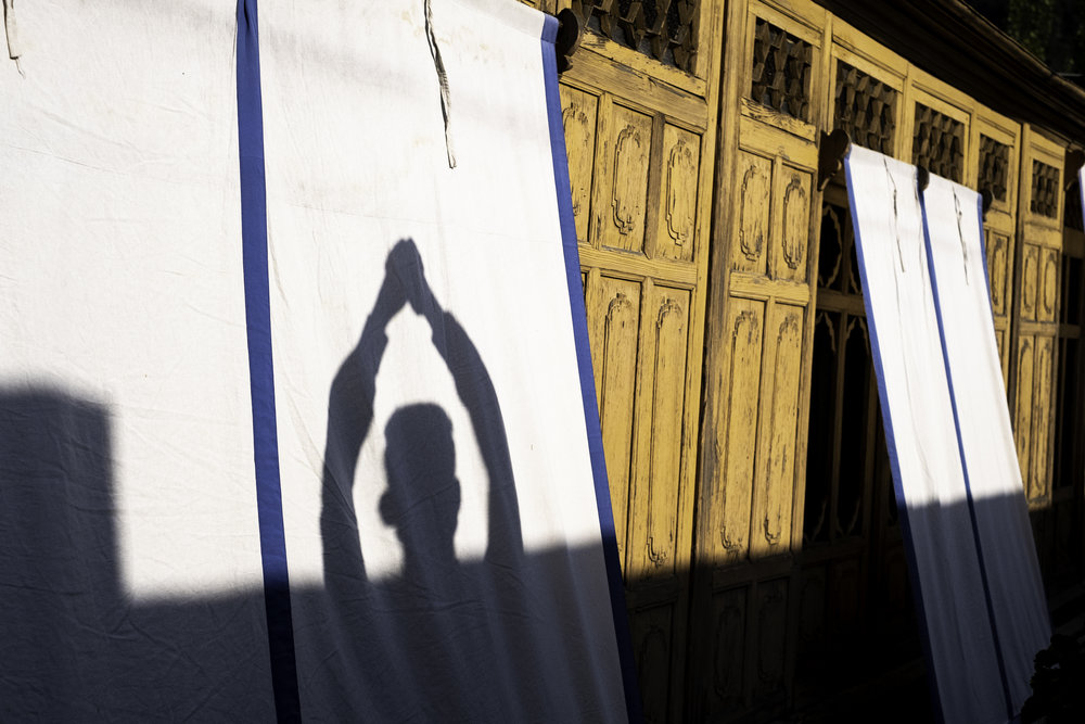 A teenaged Christian boy in Srinagar, India folds his hands in prayer in the afternoon Sun. In the 99.5% Muslim state of Kashmir, he stated that all of his friends were devout Muslims, and that Christians in the area must meet in secret to avoid death and arrest by the religious police. (Name and identity has been withheld for the subject's safety)       Srinagar, Kashmir, India. 2018.