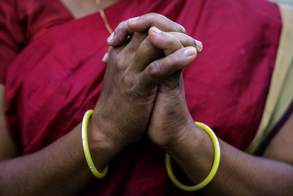 A widow in Kandhamal, India, folds her hands in prayer. During the Summer of 2008 a mob of Hindu nationalists aligned with Prime Minister Narendra Modi's BJP party, murdered her husband before her eyes for their Christian faith. After 10 years, she along with other widows who faced the same fate, still gather together to encourage each other, and worship Jesus Christ together.       Kandhamal, India. 2018
