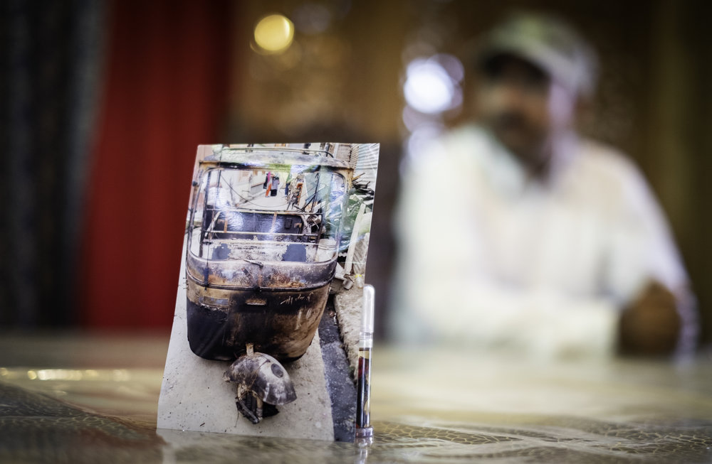 Abel, a Christian taxi driver from Srinagar, displays a photograph of his taxi that was destroyed by a group of Kashmiri Muslims after his faith was made public. He must now rent taxi's, which limits his income to provide for is family. (Real name and identity has been withheld for the subject's safety)       Srinagar, Kashmir, India. 2018.