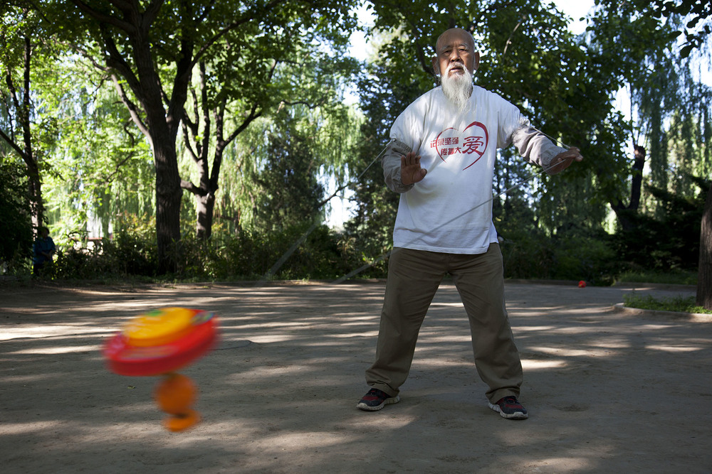 Man takes his morning exercise by turning a spinning top in Zizhuyuan Park.