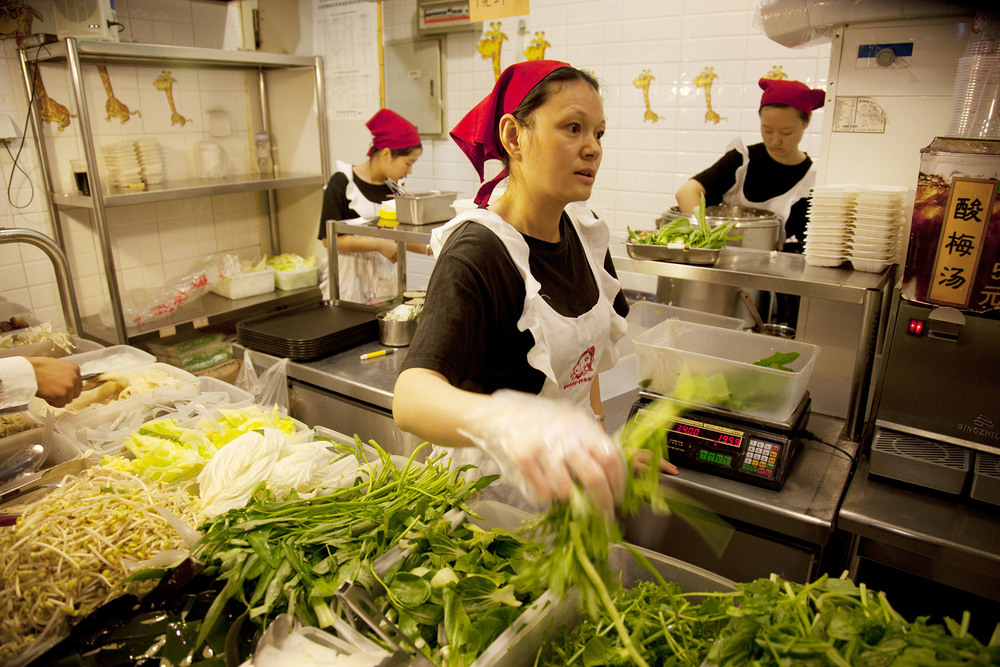 Restaurant workers serving meals on the canteen food hall floor of the e-plaza digital shopping mall.
