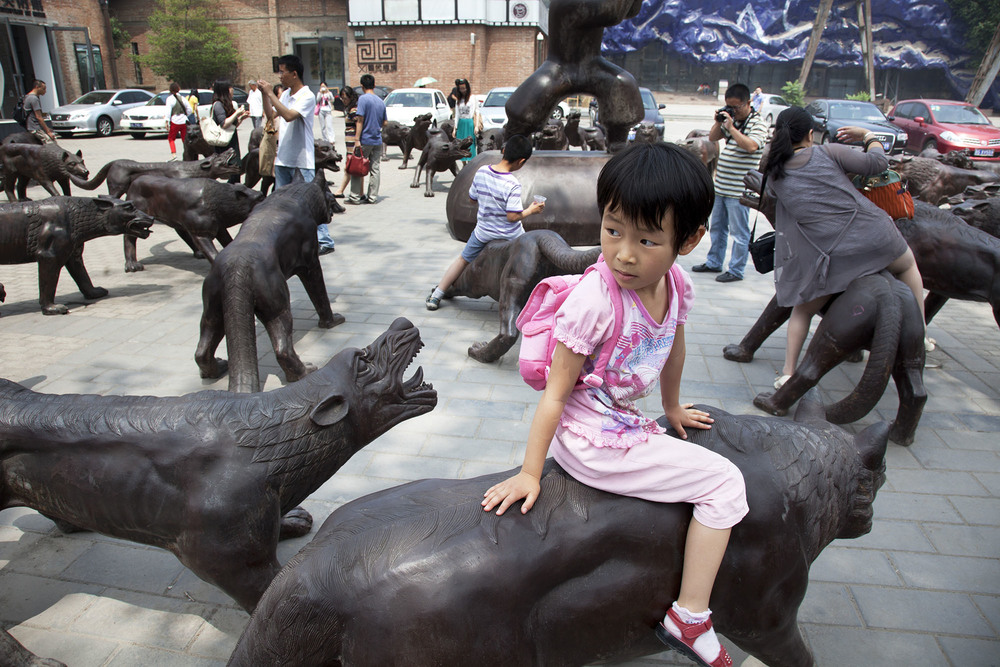Kids playing on some bronze wolf sculptures at 798 Art Zone or Dashanzi Art District.