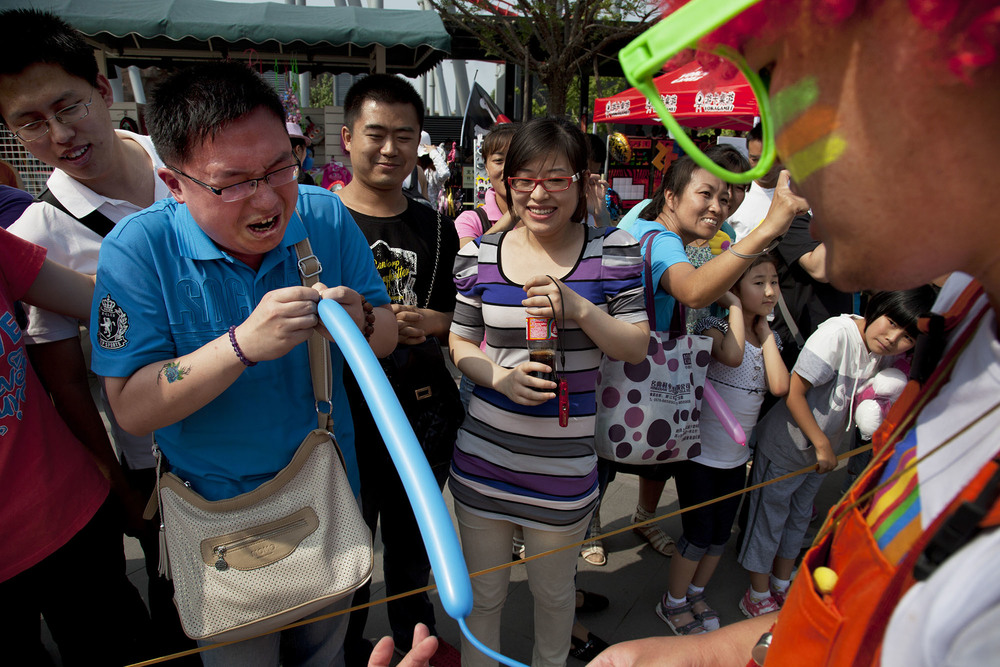 Clown asks a member of the public to blow up a long thin balloon, which he struggles to do, at Happy Valley amusement park.
