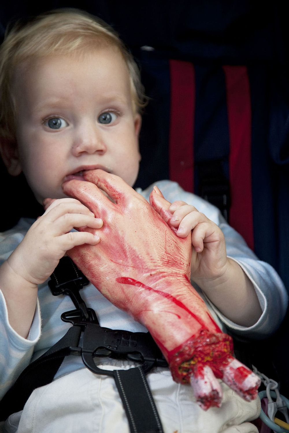 A young protester at the Stoke Newington Zombie-a-thon plays with a joke severed hand.