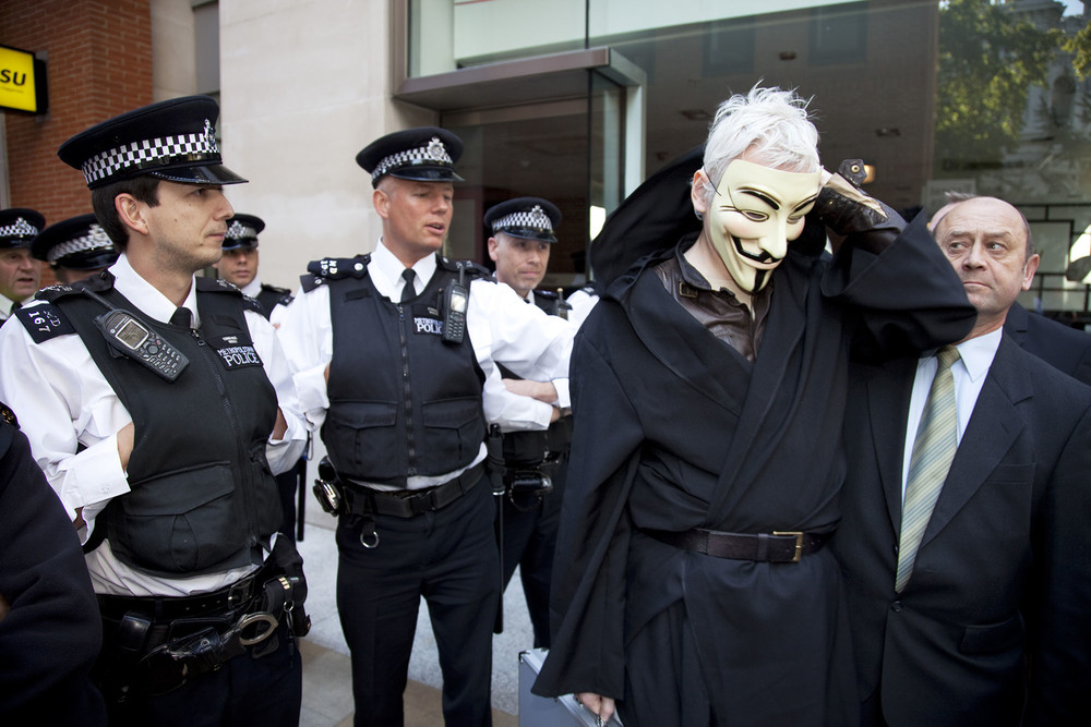 Julian Assange is de-masked and questioned by police during the Occupy London demonstration.