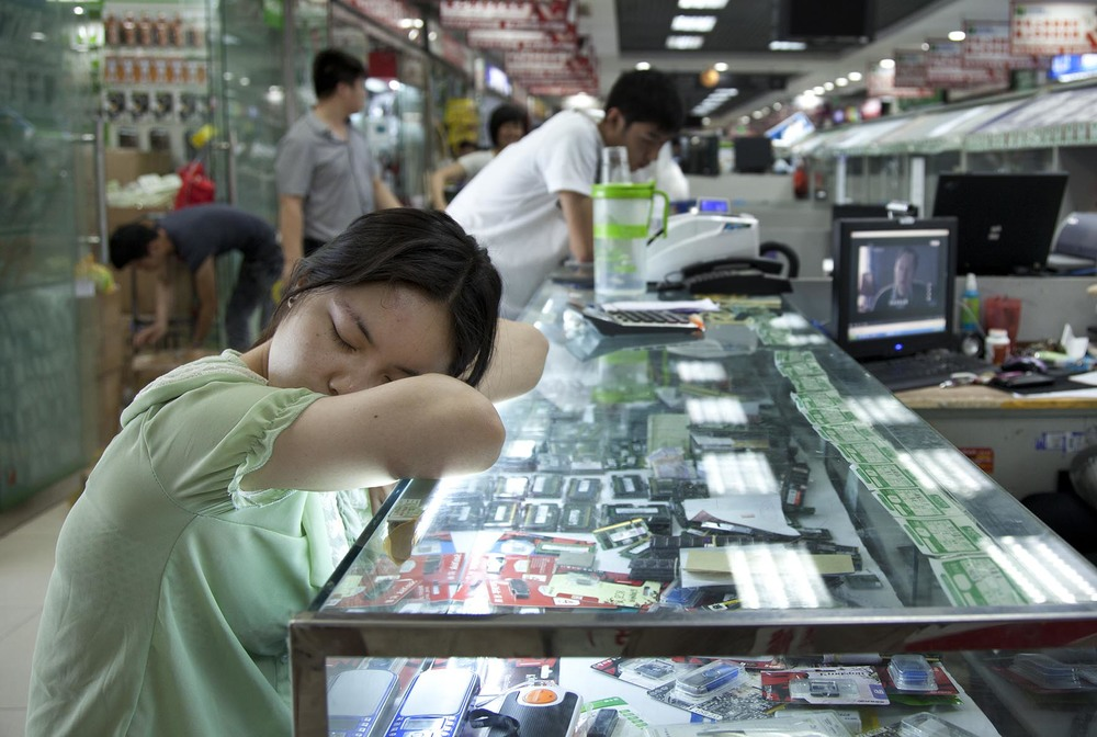 Computer seller asleep inside e-plaza digital square shopping mall Zhongguancun.