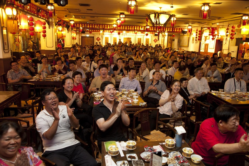 Customers sit enjoying the show, applauding and shouting at Laoshe teahouse