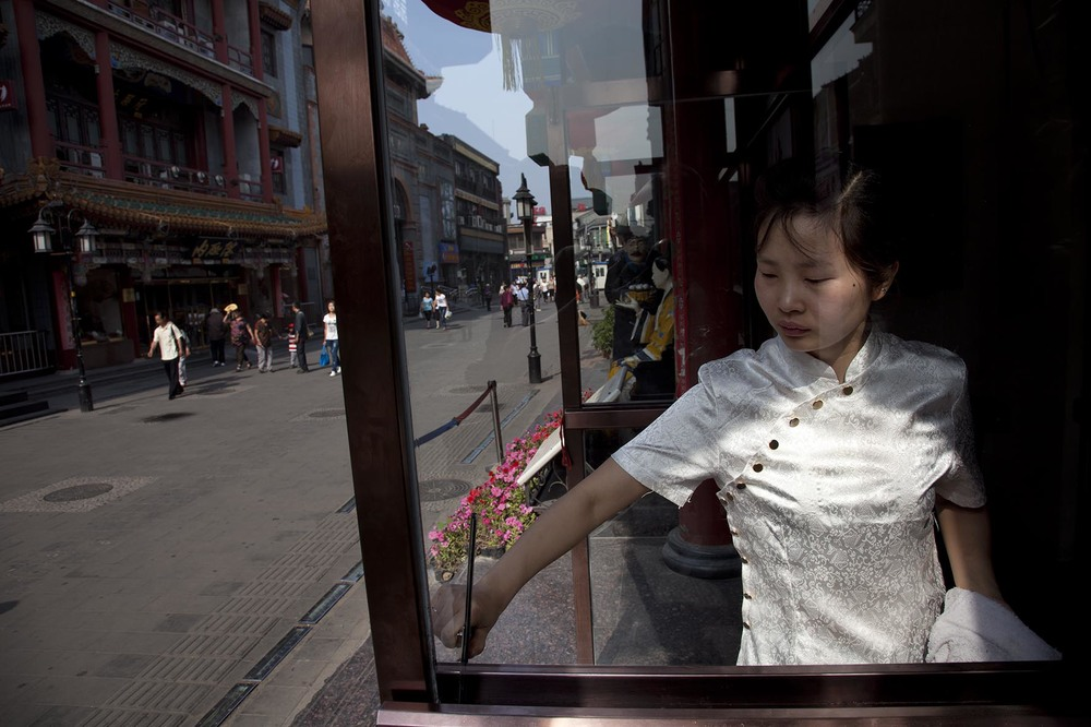 Waitress cleans the windows of a Chinese restaurant in an area just south of Tiananmen.