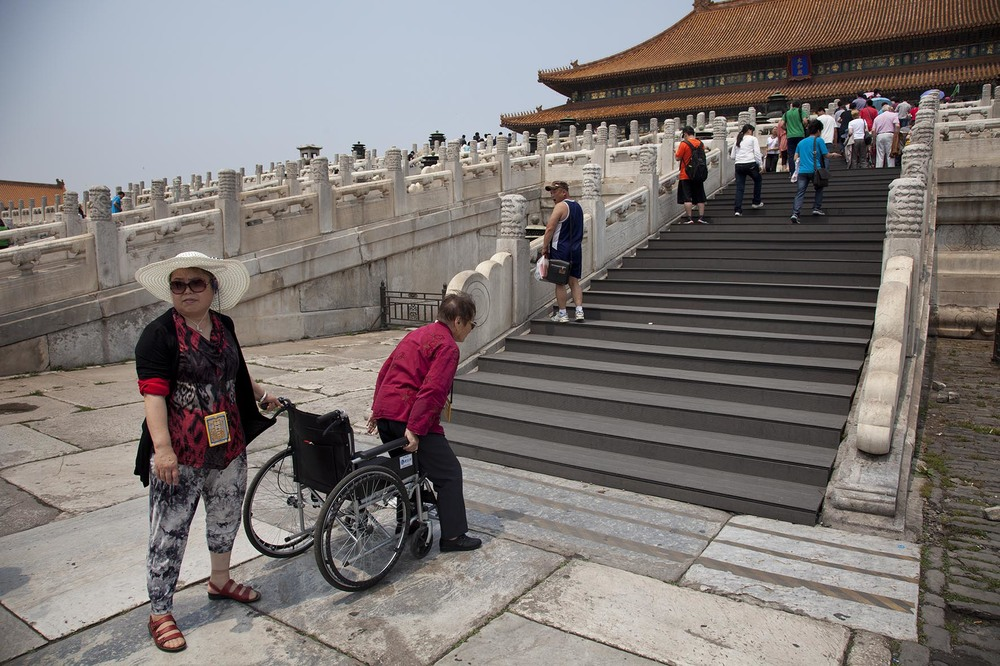 Elderly woman gets up from her wheelchair to climb the steps to the Hall of Supreme Harmony inside The Forbidden City, Beijing.