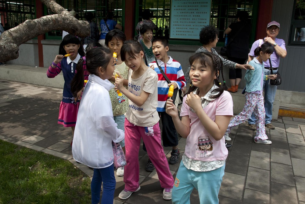 Group of young girls laugh at one of their friends after she makes an amusing error on National Children's Day in Zhongshan Park.