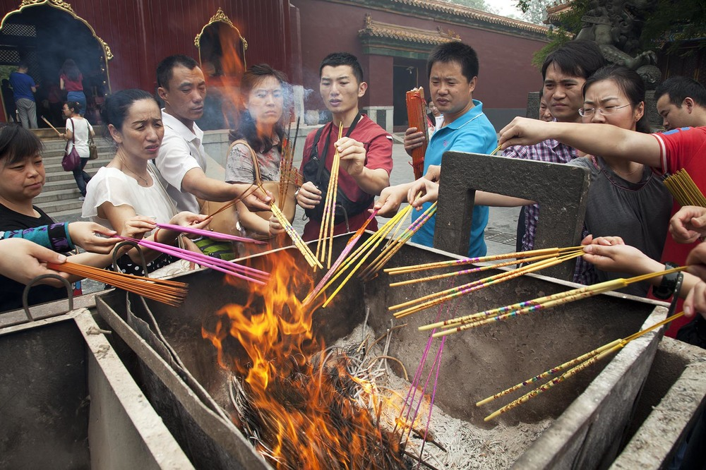 "People come to pray and burn incense sticks at The Yonghe Temple, also known as the ""Palace of Peace and Harmony Lama Temple""."