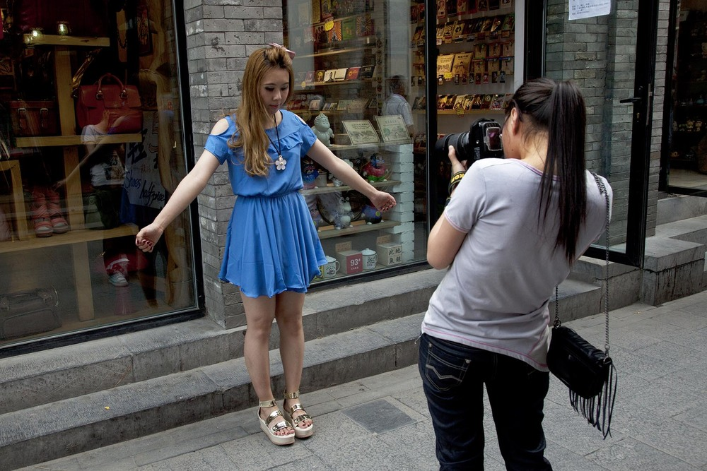 Model being photographed front and back for a fashion blog on Yandaixiejie Street.