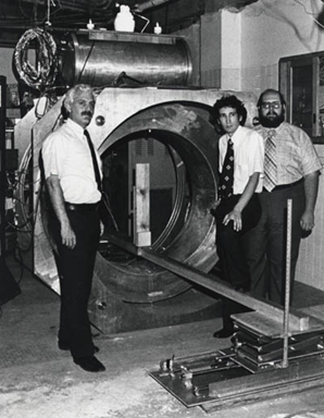 "Raymond Damadian, Larry Minkoff and Michael Goldsmith with ""Indomitable"" and its iced liquid helium and liquid nitrogen ports: the world's first supercooled, superconducting MR scanner and the world's first MRI machine."