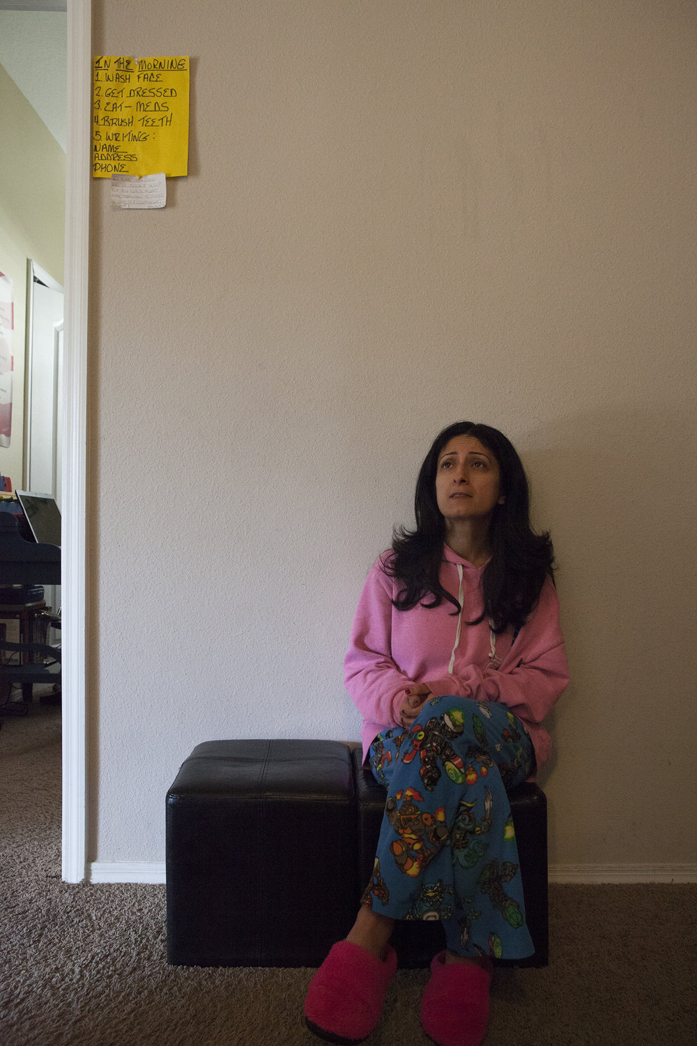 Renee in the early morning, sitting outside of Branden's room. Above Renee on the yellow sheet of paper, is a list of things for Branden to remember to do in the morning; wash his face, get dressed, take his meds, brush his teeth, and to write his name, address, and phone number. Tampa, FL.