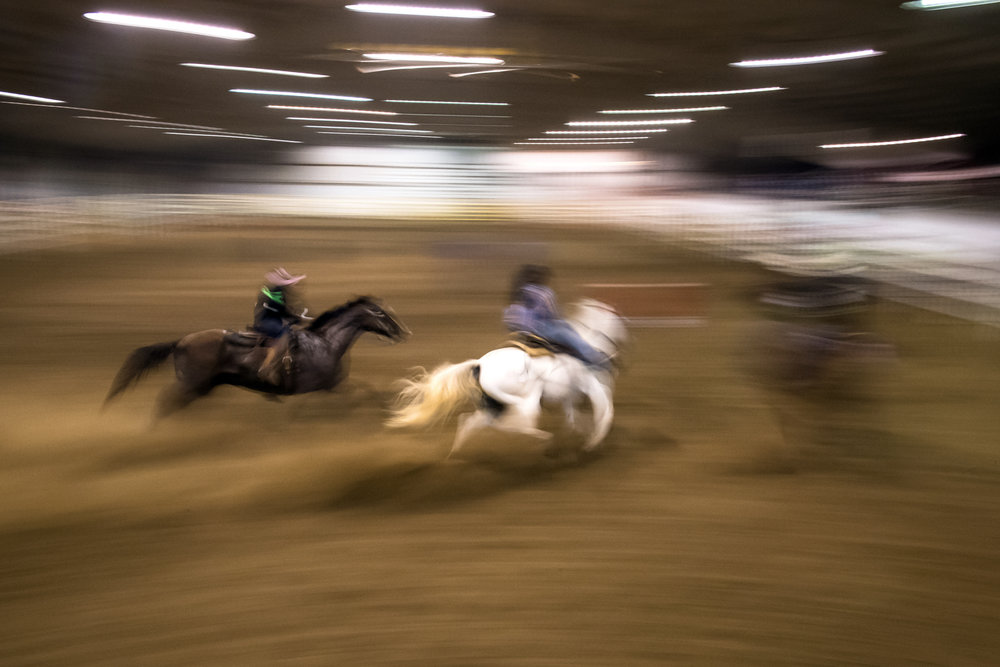 Relay race competitors speed around a corner at the rodeo arena in Greenville, Mississippi.