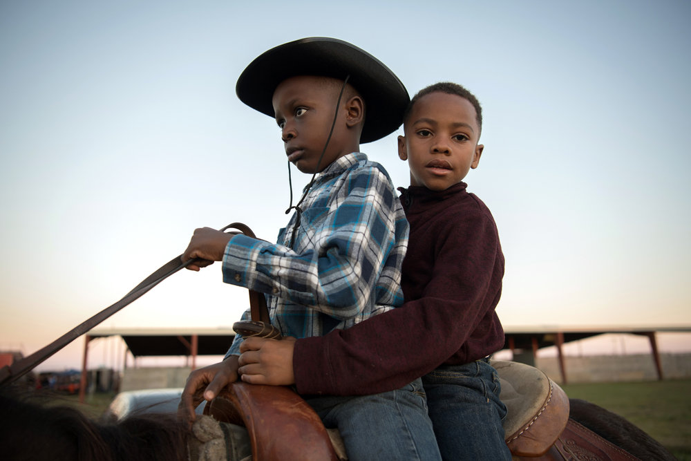 Dkamyion and Carlos ride a horse together outside a horse show in Greenville, Mississippi.