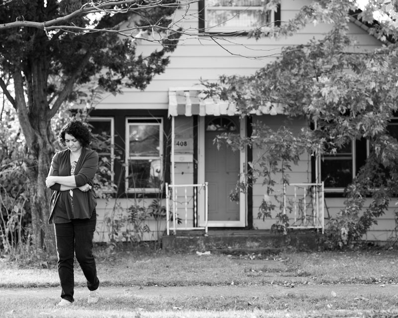 Cindy, his daughter and primary caregiver, walks away from her dilapidated childhood home in Northlake, Illinois.