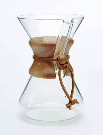 "COFFEE AWARENESS MONTH, DAY 4: Smooth Style, Smooth Substance   Behold the Chemex Coffee Brewer. Invented nearly 70 years ago by a somewhat mad scientist, this simple-yet-elegant piece of glass still makes some of the best brewed coffee around. Available in 3-cup, 6-cup, 8-cup and 10-cup sizes, all you need is the vessel ($50 or less), hot water, and the specialized Chemex filters ($10 or so for 100).    You might be thinking, ""That's a lot of money for filters!"" But the filter is the actual innovation: Made from ultra-heavy paper and then oxidized to reduce paper taste, Chemex filters block almost all the oils, sediment and ""fines"" that make their way into most other brews — and the result is the cleanest, lightest-bodied coffee that you can make.    Like coffee with your cream and sugar? Then the Chemex may not be for you. But if you want a pure coffee experience with a side of modernist style, then a Chemex should definitely be in your brewing arsenal. It's a great conversation piece (and can double as a fabulous vase — just ask my wife!) and works well regardless of whether you want coffee for one or for four. Just grind ""medium"" (think the size of cracked pepper) and slowly add hot water — it takes about 4 minutes, but it's well worth the time and effort. You'll taste nuances in your coffee that you've never noticed before, and cleanup is a breeze. 70 years old, but it tastes new every morning to us.  For more on the Chemex, including a pretty good brewing guide, check out this 2010 article in the New York Times.    Visit us at 1 p.m. this Saturday for ""Better Brewing at Home,"" a free demonstration and tasting at Spencer's Coffee. We'll be brewing with the Chemex, as well as one or two other devices, and experts will be on hand to answer any questions or concerns!"