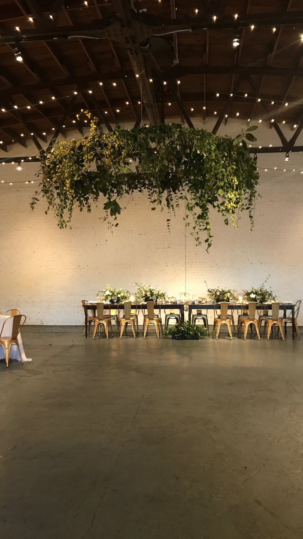 "Brickyard in Marietta is such a cute little space. They offer this very large (10-12 foot wide) hoop for all of their clients. We decided to ""green"" the entire thing with all foraged greenery and a little bit of ""hops"". Yes, ""hops"" like what is in beer. Luckily, the hoop is able to be lowered so we didn't have a whole lot of ladders involved but we did lots of foraging and balancing to make this a statement piece. Image is by me!"